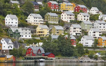 Traditional norwegian fjord village with colored houses and forest